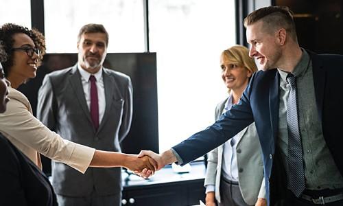 Geschäftsleute schütteln sich die Hand beim Bewerbungsgespräch